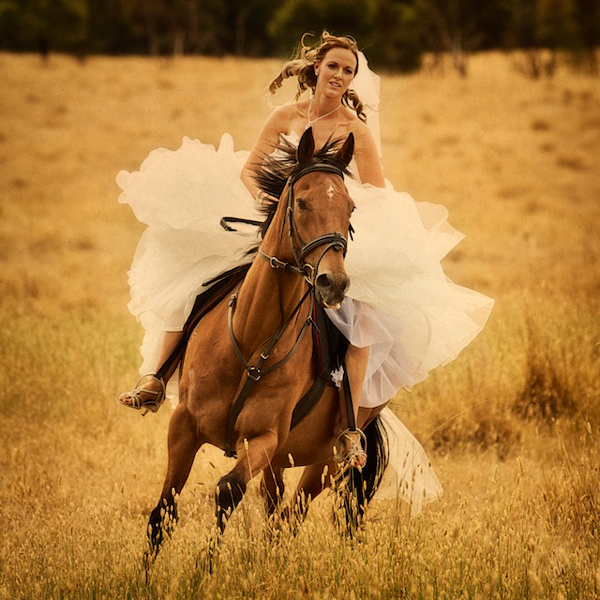 Beautiful bride horse back riding in country wedding