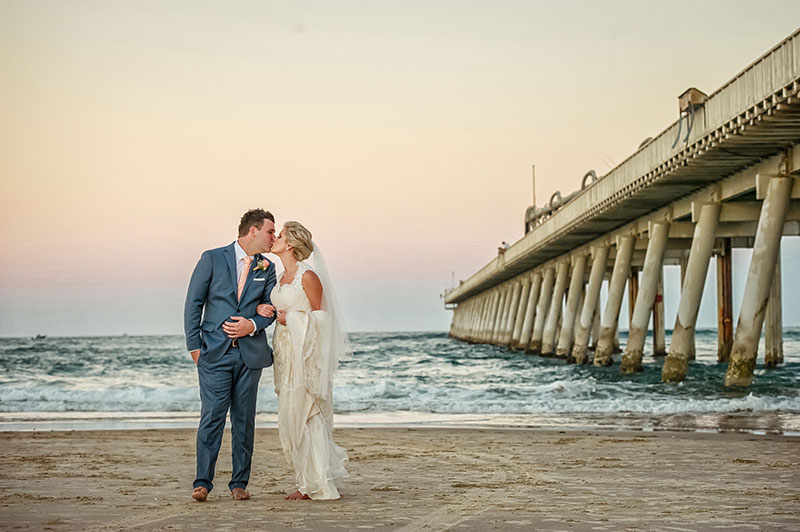 Bride and groom kissing next to pier at Surfers Paradise beach.
