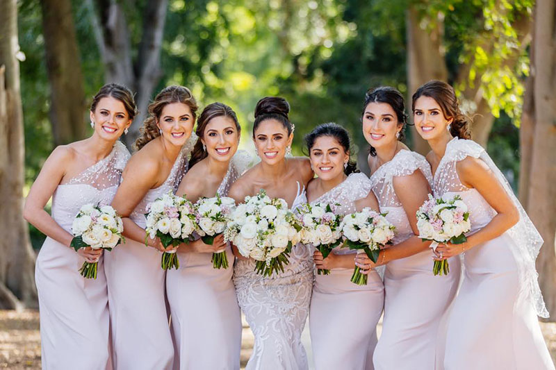 Bride and bridesmaids holding white bouquets from Brisbane Market Flowers.