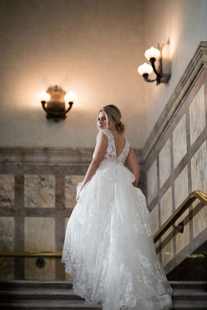 Bride walking up stairs in a traditional wedding gown by Fiorenza.