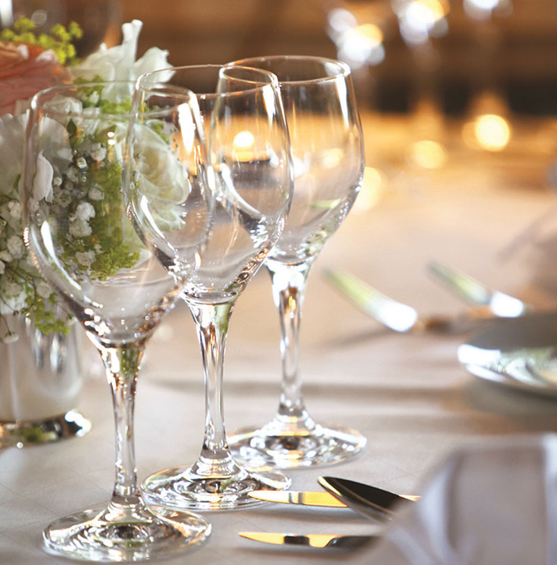 Wine glasses on a table set for a wedding reception at the Hellenic Club.