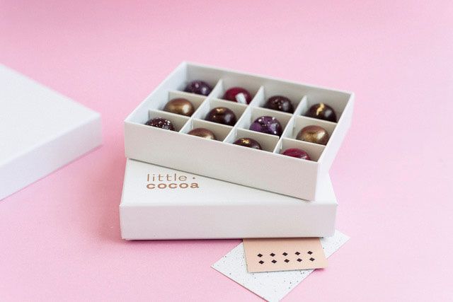 Twelve exquisite handmade chocolates in a white gift box with the name Little Cocoa on the box, on a pink background