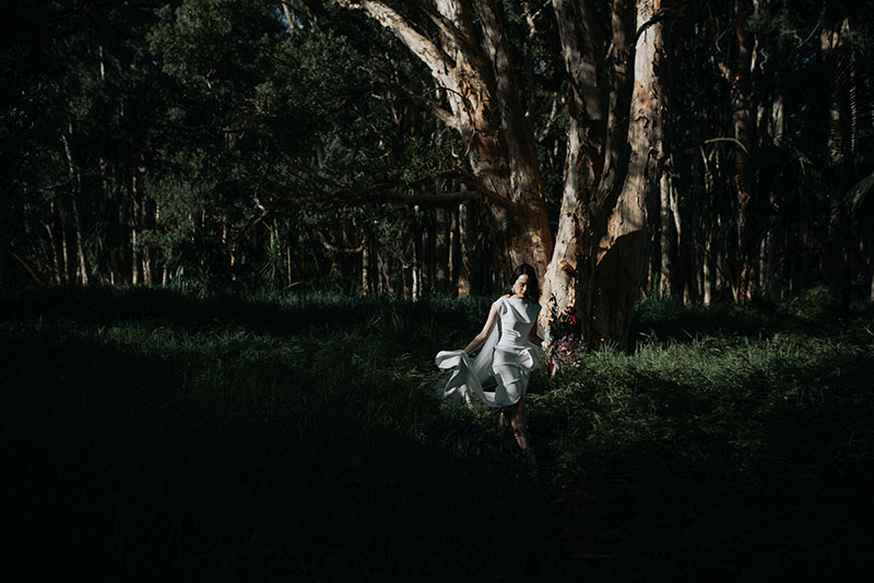 Moody photo showing a bride holding flowers walking near trees in the dark.