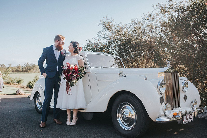 Bride and Groom pose in front of a white, classic Rolls Royce.