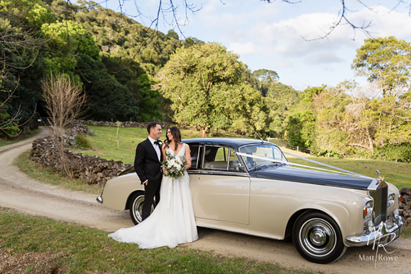 Bride and Groom pose in front of a Champagne and Black Bentley in a countryside setting.