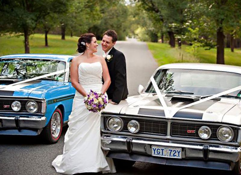 Bride and Groom pose in front of two Falcon GT's.
