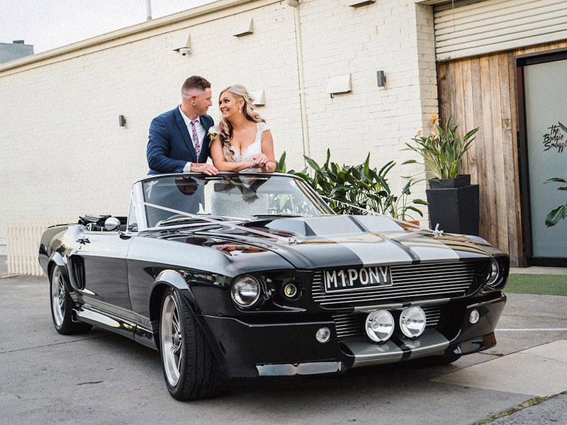 Bride and Groom standing in a black Mustang.