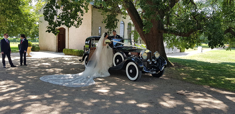 Bride getting into a black 1935 Rolls Royce parked under a large shady tree.