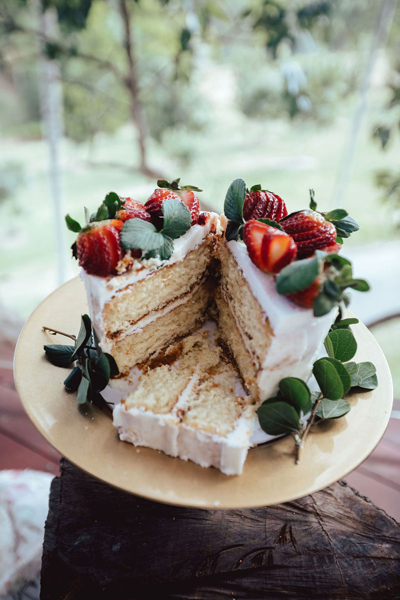 Photo by DK and Co. Photography of cake with white glaze and strawberries.