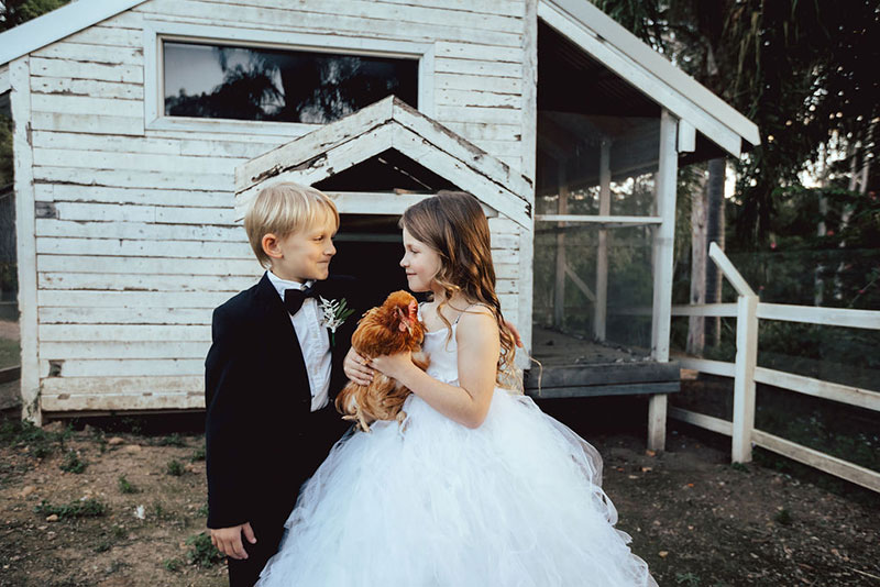 Photo by DK and Co. Photography of kids at wedding holding chook in chook pen.