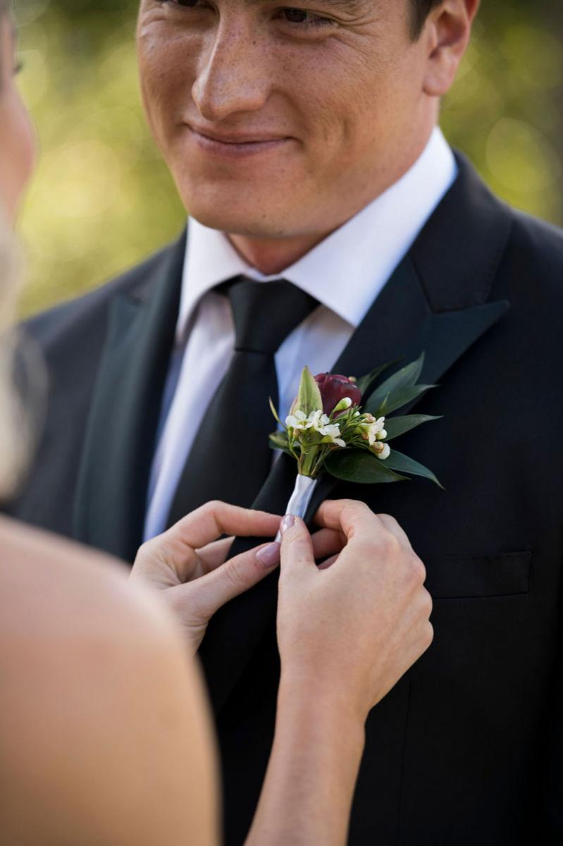 Photo taken by Leigh Warner Weddings of a Groom looking at Bride while she fixes the flower on his suit..