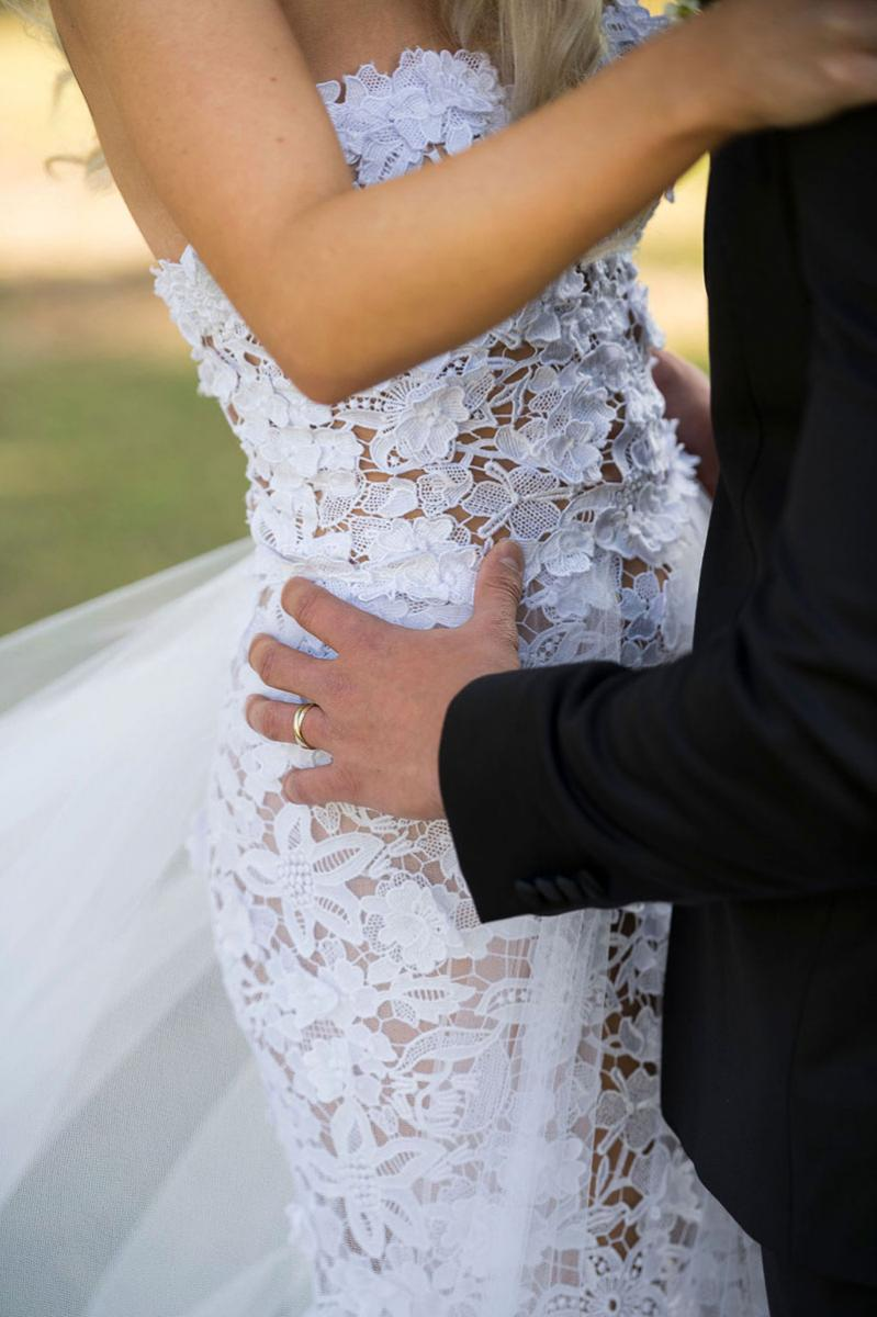 Photo taken by Leigh Warner Weddings of a Bride in a lace gown with the Grooms hands on her hips.