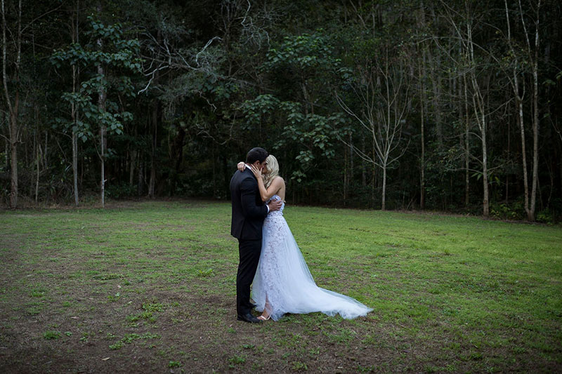 Photo taken by Leigh Warner Weddings of Bride and Groom in clearing in front of rainforest setting.
