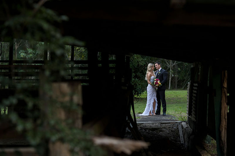 Photo taken by Leigh Warner Weddings of Bride and Groom framed by a shed in the foreground.
