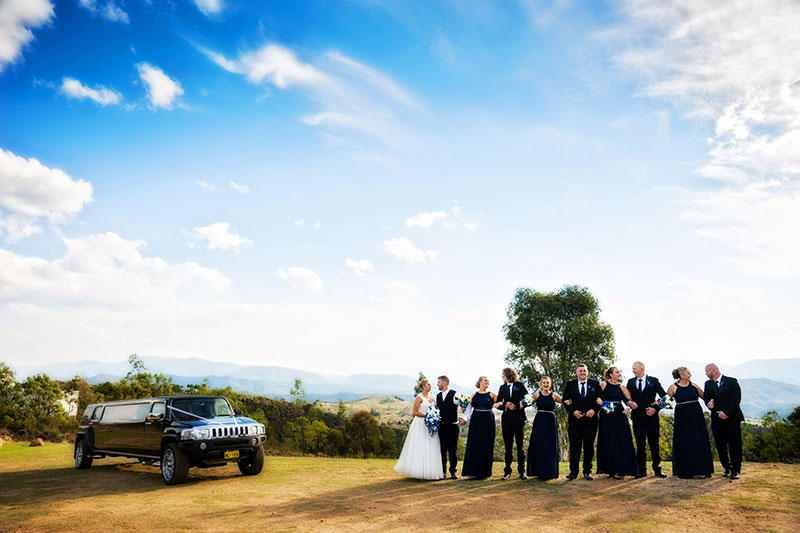 Atmospheric shot of wedding party and transport in country setting.