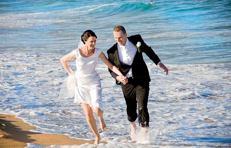 Happy bride and groom running through the water at the beach.