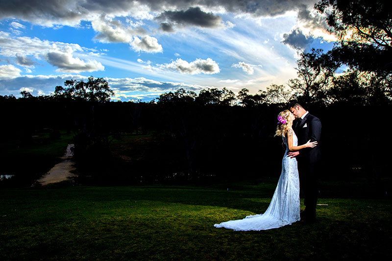 Bride and groom kissing under a vast blue sky at dusk..