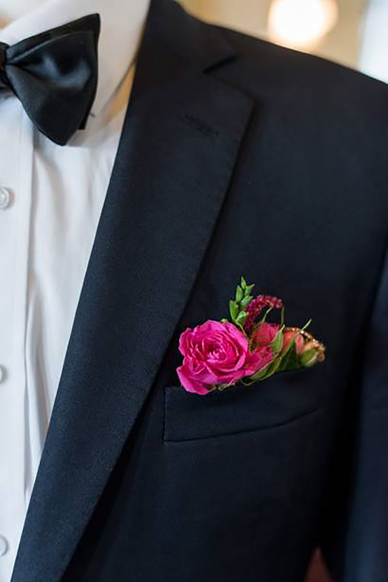 Bright flower boutonniere tucked into jacket pocket.