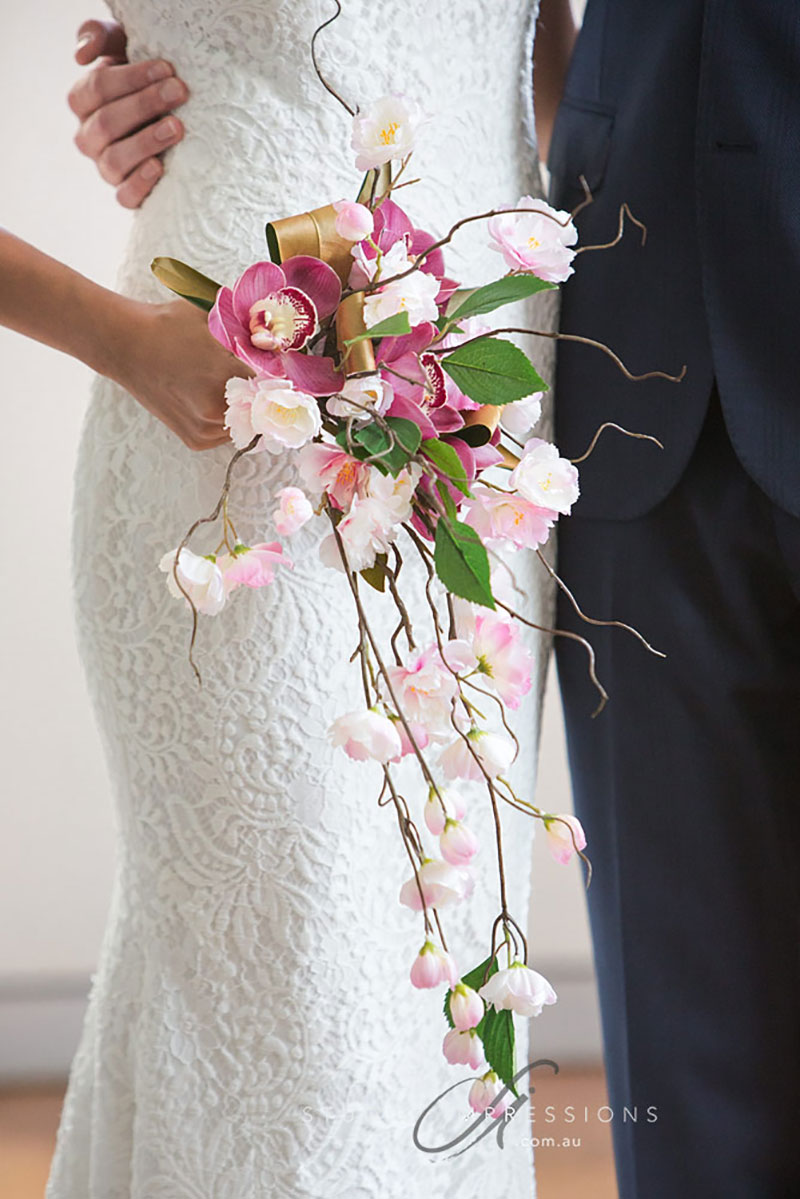 Bride holding a combined silk and fresh wedding bouquet.