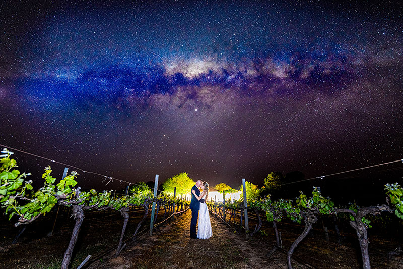 Bride and Groom hugging under a beautiful starry night sky.