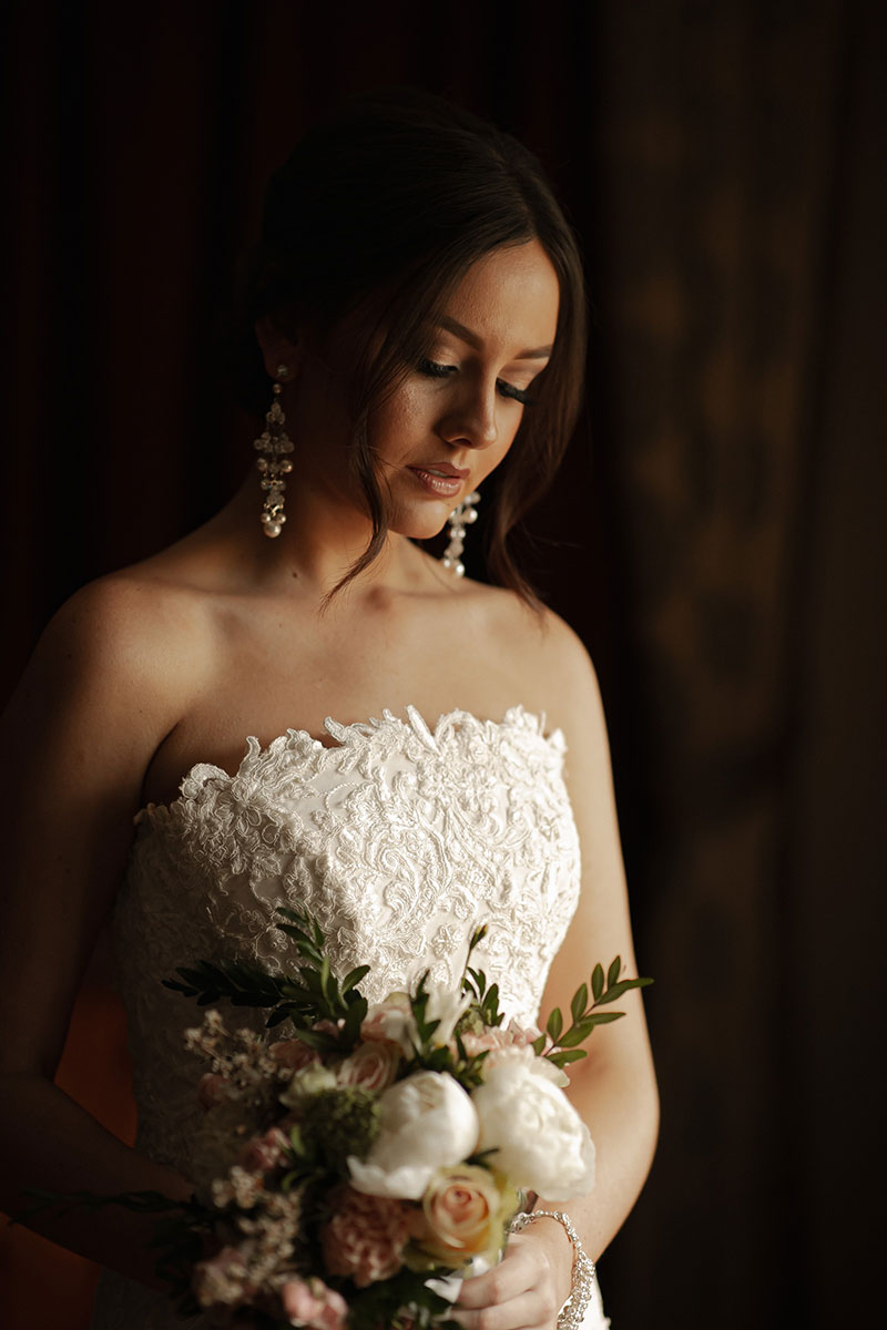 Photo by Tom Judson Photography of Bride holding flowers and looking pensive.