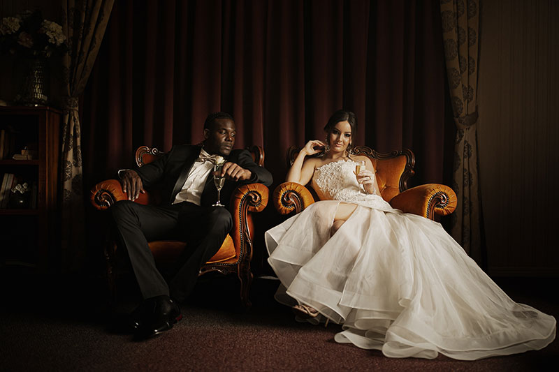 Photo by Tom Judson Photography of Bride and Groom relaxing with champagne on ornate chairs.