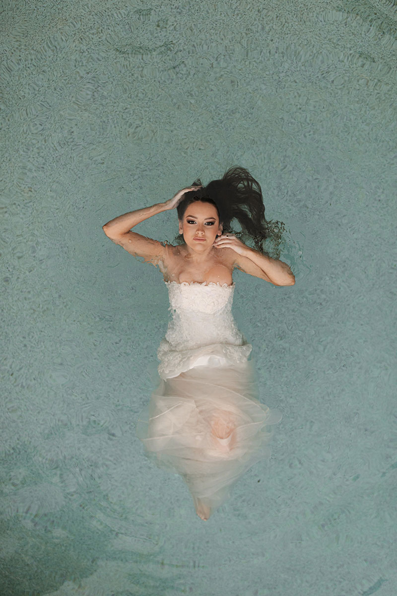 Photo by Tom Judson Photography of model wearing wedding gown in pool.