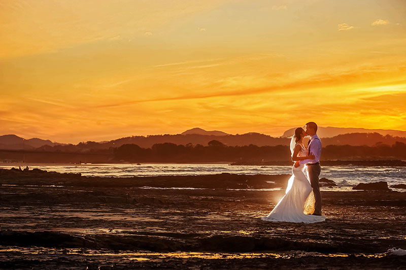 Bride and groom together on beach with golden sunset.