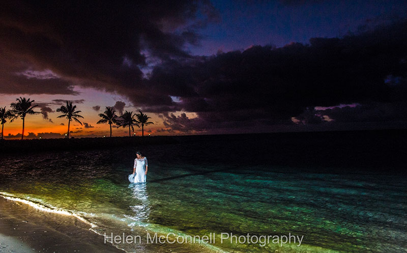 Colourful sunset overhead with bride in the sea.