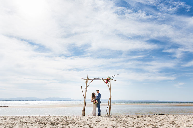 Bride and groom under a simple arbour on beach.