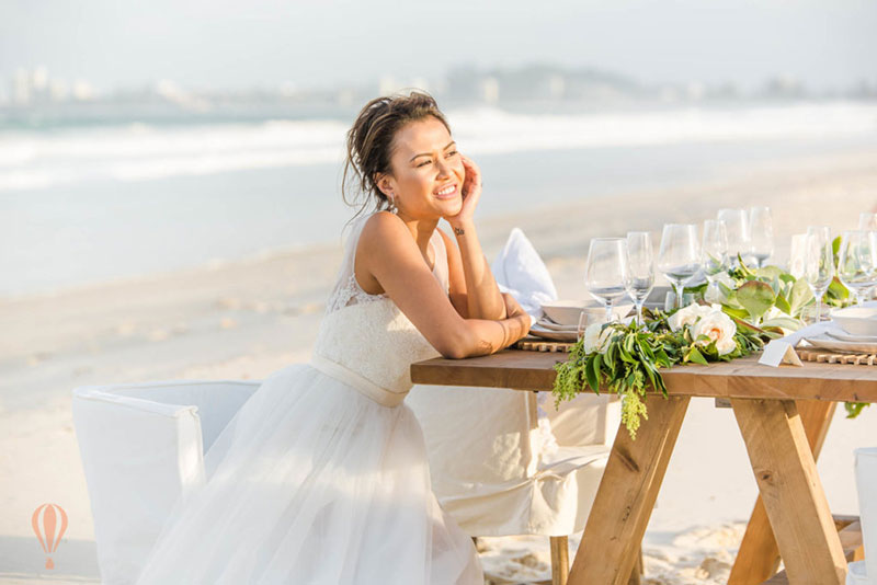 Happy bride sits smiling at reception table set up on beach.