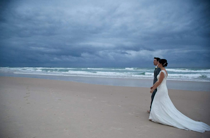 Bride and groom at the beach under a threatening sky.