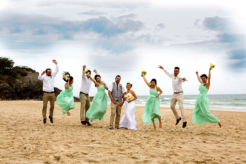Happy wedding party with bright green dresses on beach.