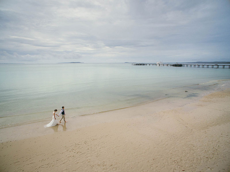 Bride and groom walking on a beautiful calm beach.