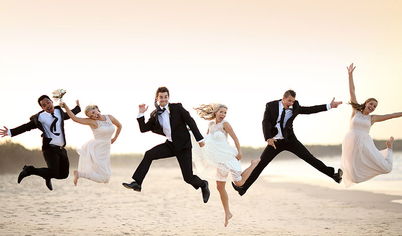 Wedding party jumping for joy at beach.