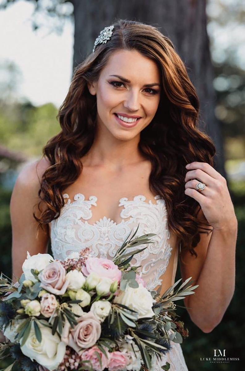 Bride with natural makeup holding flowers and smiling.