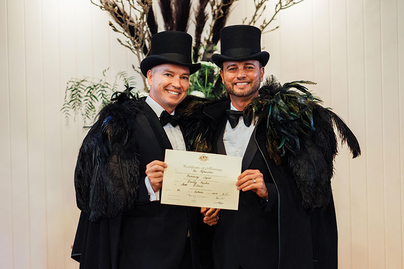 Brad and Scott happily pose with their marriage certificate at Broadway Chapel.