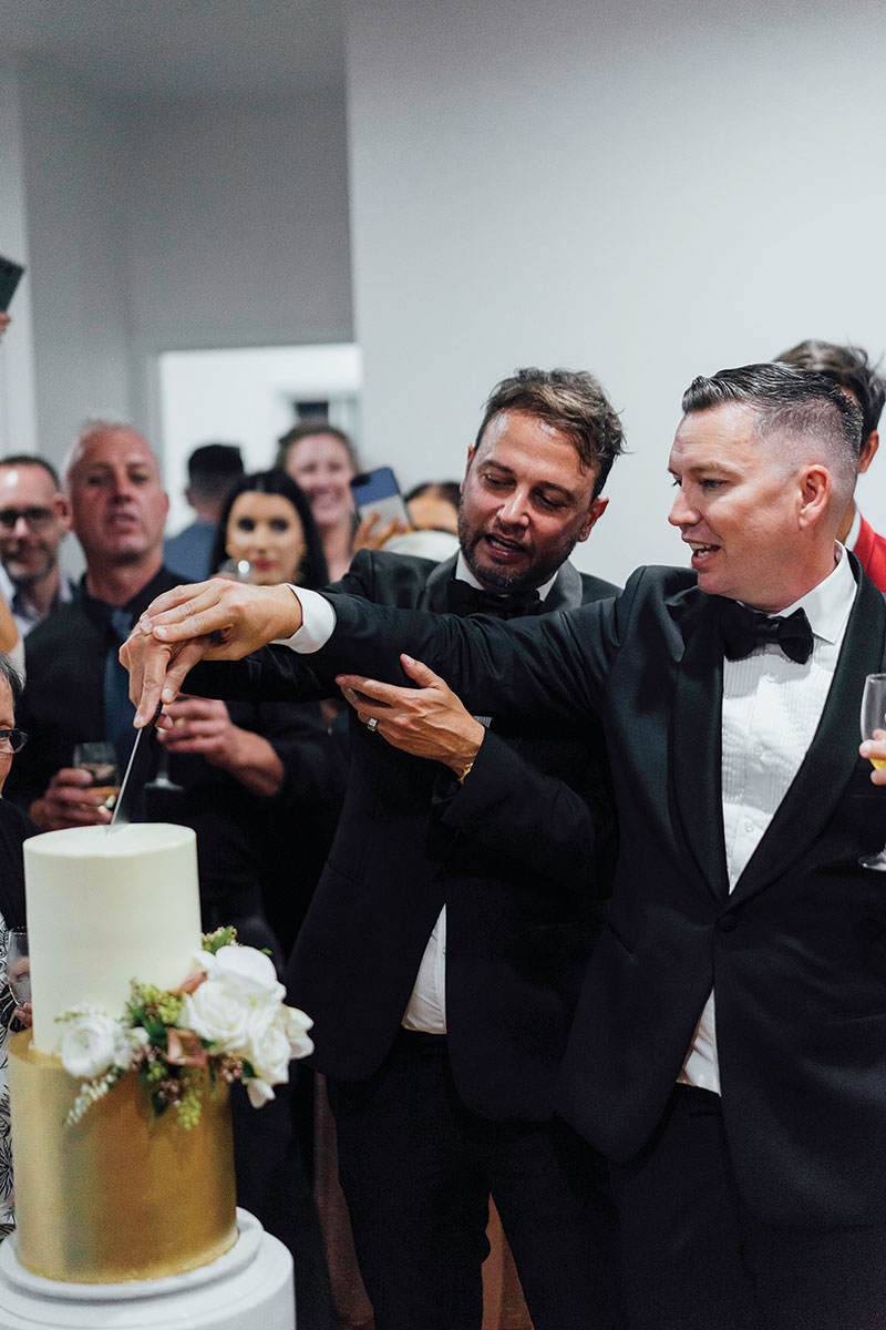 Brad and Scott with their guests, cutting their wedding cake.