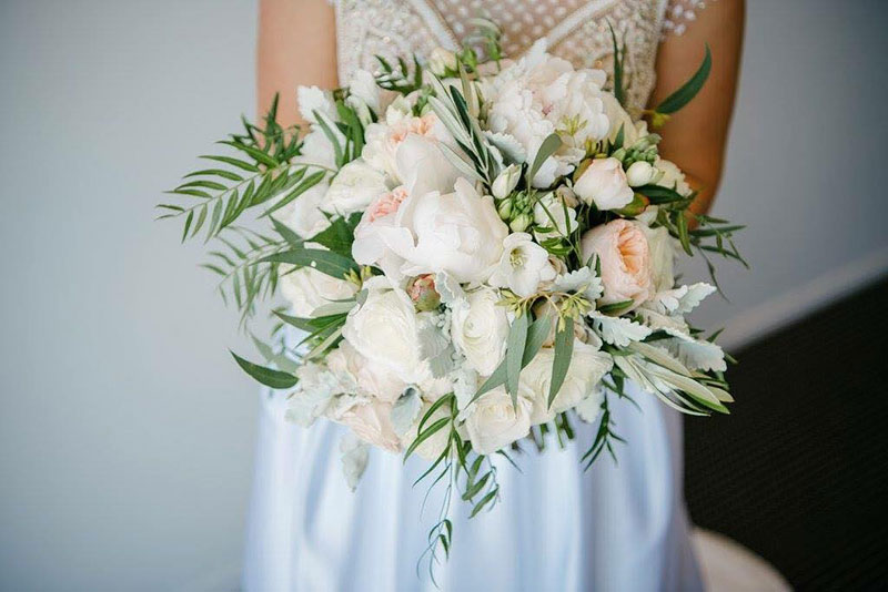 Bride holding a large bouquet of ivory wedding flowers.
