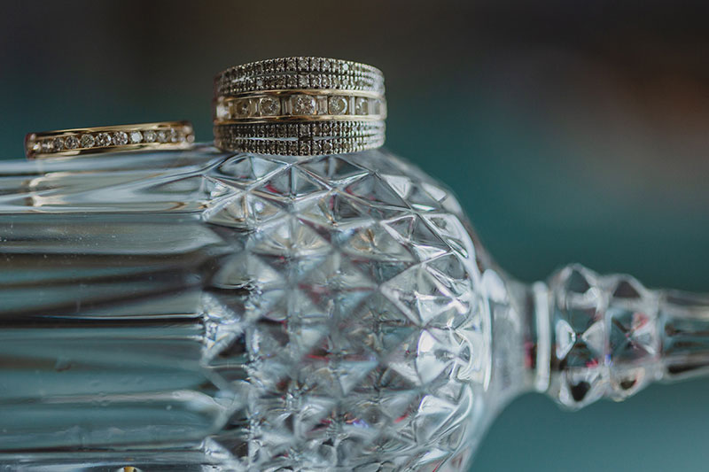 Crystal bottle with wedding rings on top.