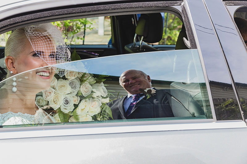 Smiling bride arrives at Broadway Chapel in a Mercedes Benz.