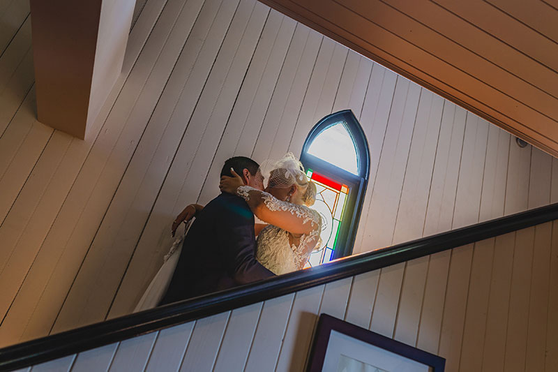 Bride and groom kiss in front of stained glass window at Broadway Chapel.