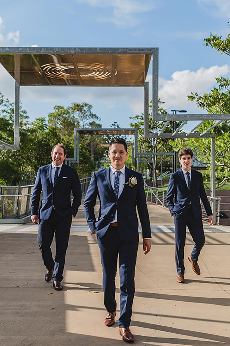 Groom and his two groomsmen in their dark blue suits.