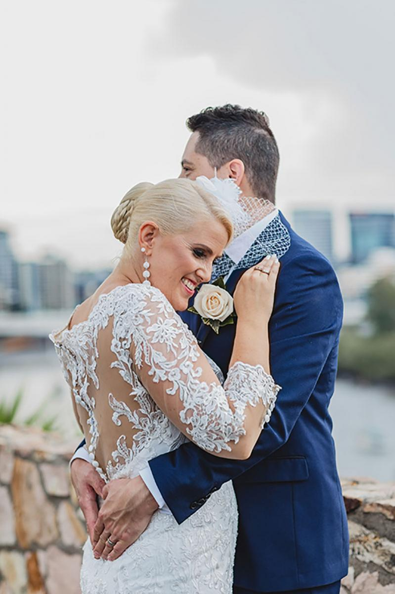 Bride and groom hugging with Brisbane city in the background..