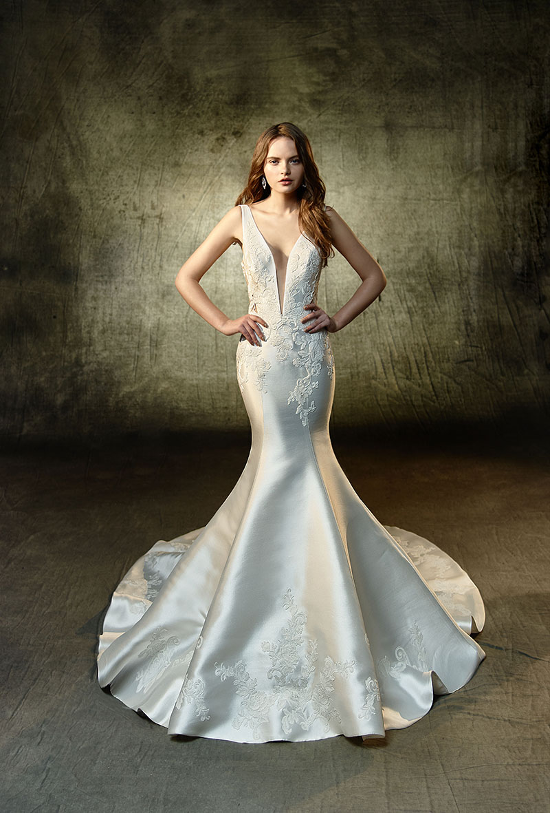 Bride wearing a low-cut, sleek wedding gown from Enzoani Collection.