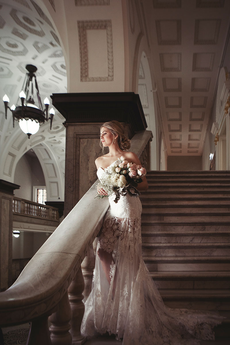 Bride wearing a Fiorenza wedding gown standing on stairs