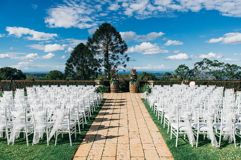 Outside wedding ceremony with white chairs at Flaxton Gardens.