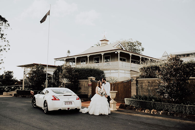 Bride and groom with wedding car outside Flaxton Gardens.