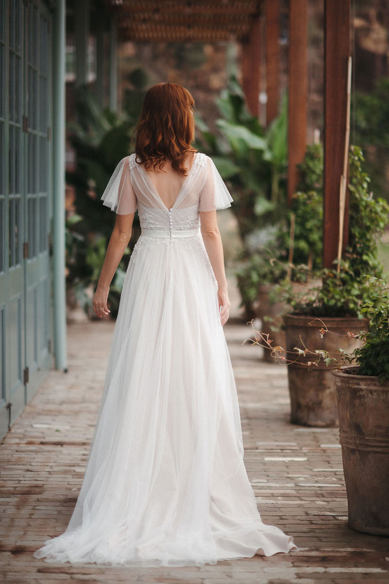 Rear view of a red-haired bride wearing Dahlia from French by Wendy Makin.
