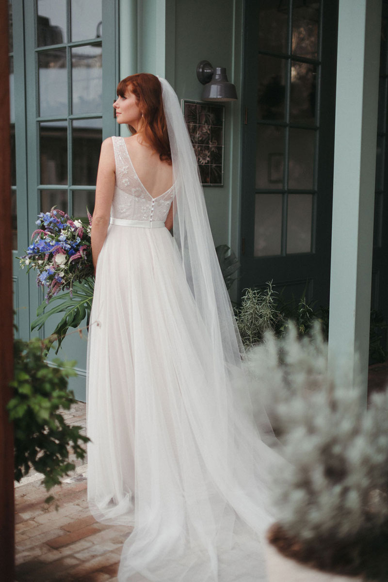 Rear view of a bride wearing a gown from French by Wendy Makin and holding flowers.